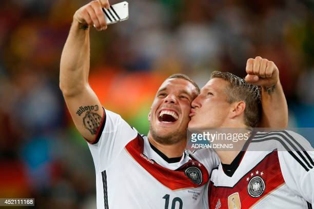 Germany's midfielder Bastian Schweinsteiger and teammate forward Lukas Podolski take a 'selfie' after their victory in extratime in the final...