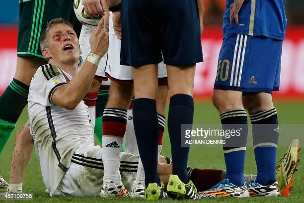Germany's midfielder Bastian Schweinsteiger bleeds after clashing with Argentina's forward Sergio Aguero during the final football match between...