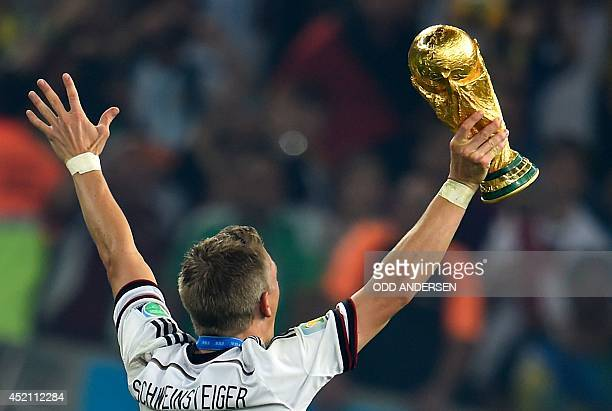 Germany's midfielder Bastian Schweinsteiger celebrates holding the World Cup trophy after winning the 2014 FIFA World Cup final football match...