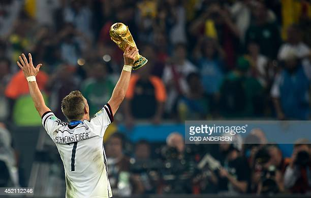 Germany's midfielder Bastian Schweinsteiger holds up the World Cup trophy as he celebrates after his team won the 2014 FIFA World Cup final football...