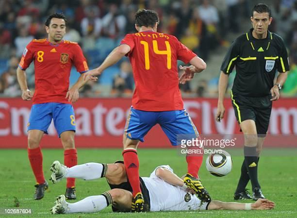 Germany's midfielder Bastian Schweinsteiger lies down as Spain's midfielder Xavi and Spain's midfielder Xabi Alonso clash during the 2010 World Cup...