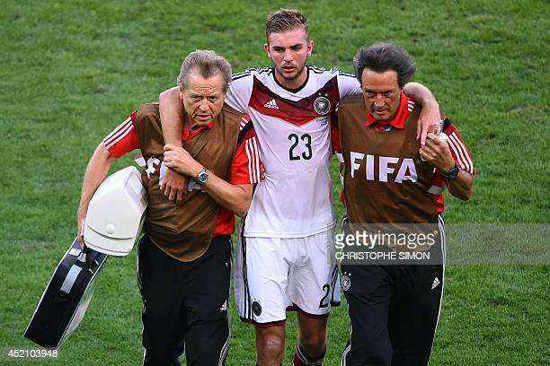 Germany's midfielder Christoph Kramer is helped from the pitch by coaching staff during the final football match between Germany and Argentina for...