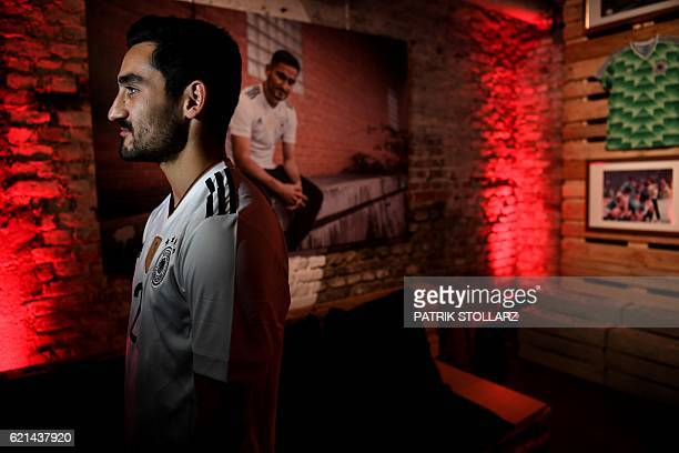 Germany's midfielder Ilkay Guendogan wears the new German national team jersey as he gives an interview after the jersey presentation in Duesseldorf,...