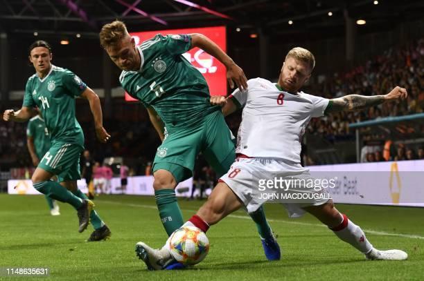 Germany's midfielder Joshua Kimmich and Belarus' midfielder Nikita Korzun vie for the ball during the Euro 2020 football qualification match between...