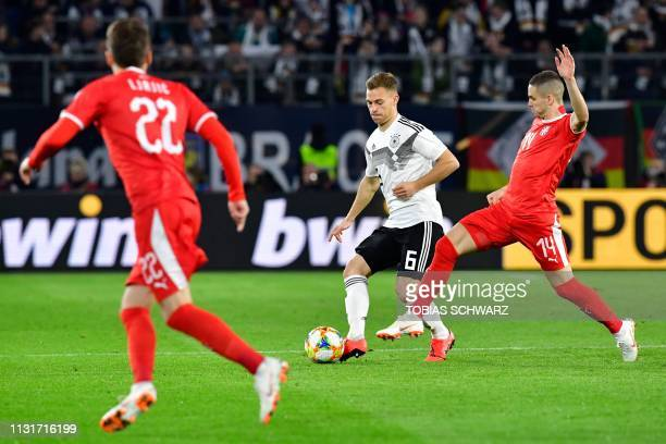 Germany's midfielder Joshua Kimmich and Serbia's midfielder Mijat Gacinovic vie for the ball during the friendly football match Germany v Serbia in...