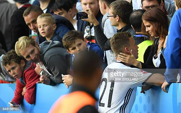 Germany's midfielder Joshua Kimmich speaks to his girlfriend Lina Meyer at the end of the Euro 2016 round of 16 football match between Germany and...