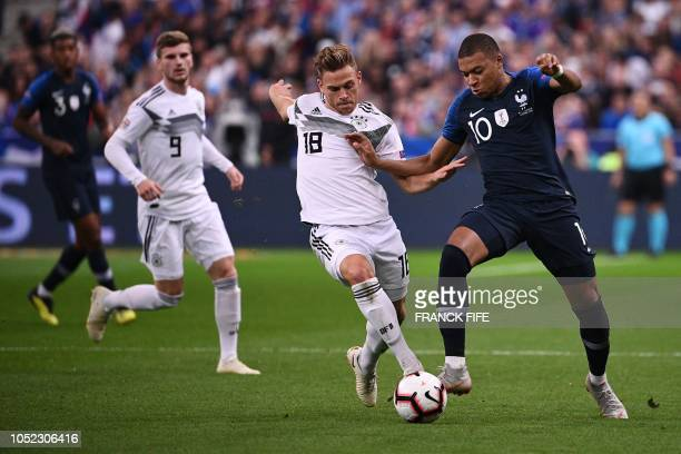 Germany's midfielder Joshua Kimmich vies with France's midfielder Kylian Mbappe during the UEFA Nations League football match between France and...