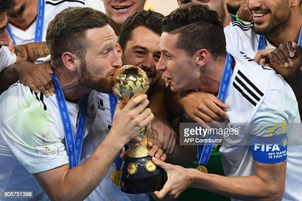 Germany's midfielder Julian Draxler and Germany's defender Shkodran Mustafi kiss the trophy after winning the 2017 Confederations Cup final football...