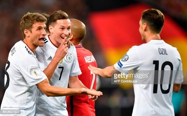 Germany's midfielder Julian Draxler celebrates scoring his side's second goal with teammates Germany's midfielder Thomas Mueller and Germany's...