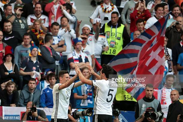 Germany's midfielder Julian Draxler celebrates with Germany's defender Mats Hummels after scoring their third goal during the Euro 2016 round of 16...