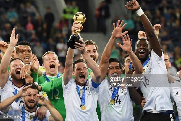 Germany's midfielder Julian Draxler lifts the trophy after winning the 2017 Confederations Cup final football match between Chile and Germany at the...