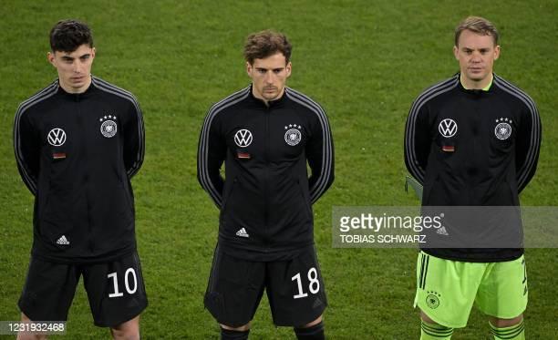 Germany's midfielder Kai Havertz, Germany's midfielder Leon Goretzka and Germany's goalkeeper Manuel Neuer listen to the anthem prior to the FIFA...