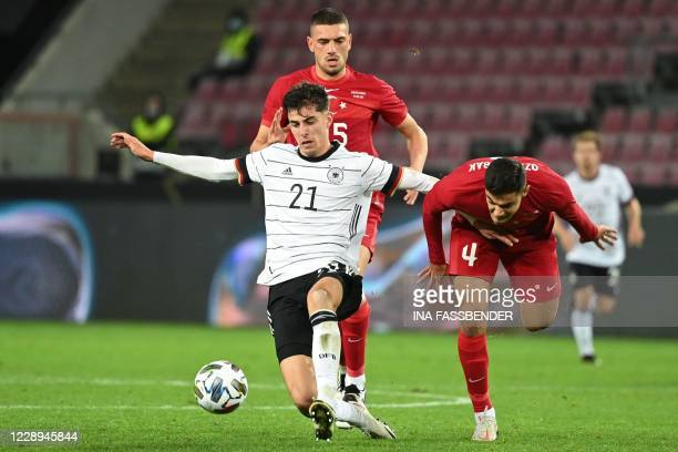 Germany's midfielder Kai Havertz vies for the ball with Turkey's defender Merih Demiral and Turkey's defender Ozan Kabak during the international...