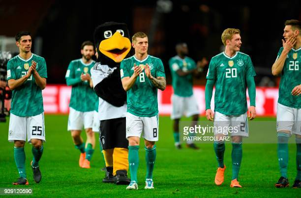 Germany's midfielder Lars Stindl midfielder Toni Kroos midfielder Julian Brandt and defender Niklas Suele applaud after the international friendly...