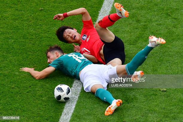 TOPSHOT Germany's midfielder Leon Goretzka and South Korea's forward Son Heungmin fall following a challenge during the Russia 2018 World Cup Group F...