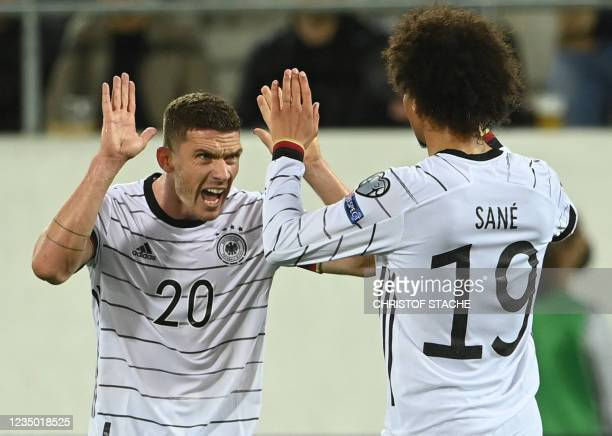 Germany's midfielder Leroy Sane celebrates with Germany's defender Robin Gosens scoring during the FIFA World Cup Qatar 2022 qualification Group J...