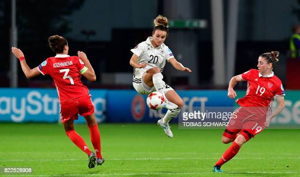 TOPSHOT Germany's midfielder Lina Magull vies with Russia's defender Anna Kozhnikova and Russia's defender Ekaterina Morozova during the UEFA Women's...
