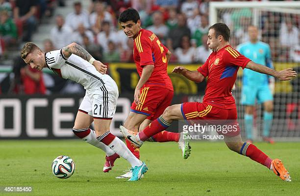 Germany's midfielder Marco Reus Armenia's defender Robert Arzumanyan and Armenia's midfielder Artur Yedigaryan vie for the ball during the friendly...
