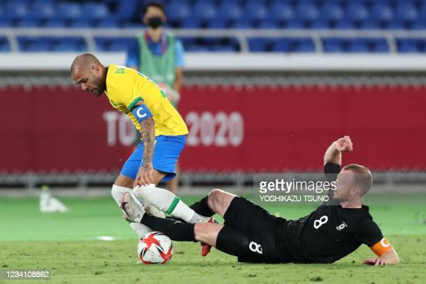 Germany's midfielder Maximilian Arnold tackles Brazil's defender Dani Alves during the Tokyo 2020 Olympic Games men's group D first round football...