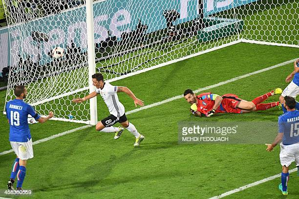 TOPSHOT Germany's midfielder Mesut Oezil celebrates after scoring during the Euro 2016 quarterfinal football match between Germany and Italy at the...