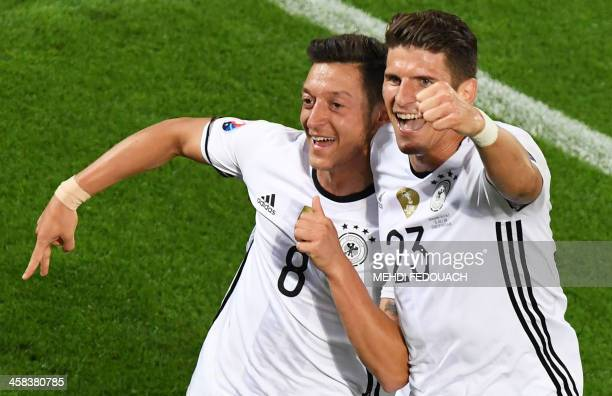 TOPSHOT Germany's midfielder Mesut Oezil celebrates with Germany's forward Mario Gomez after scoring during the Euro 2016 quarterfinal football match...