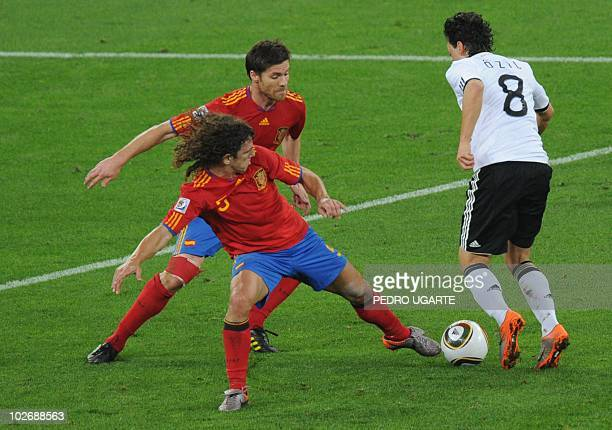 Germany's midfielder Mesut Oezil fights for the ball with Spain's defender Carles Puyol and midfielder Xabi Alonso during the 2010 World Cup...