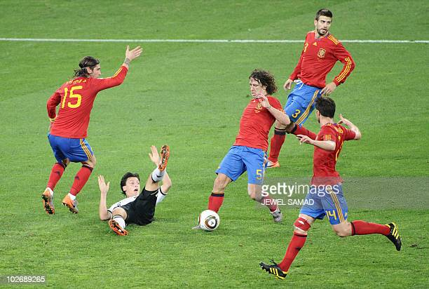 Germany's midfielder Mesut Oezil gestures on the pitch next to Spain's defender Sergio Ramos Spain's defender Carles Puyol Spain's defender Gerard...