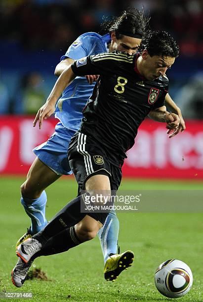 Germany's midfielder Mesut Oezil is chased by Uruguay's striker Edinson Cavani during the 2010 World Cup third place football match Uruguay vs...