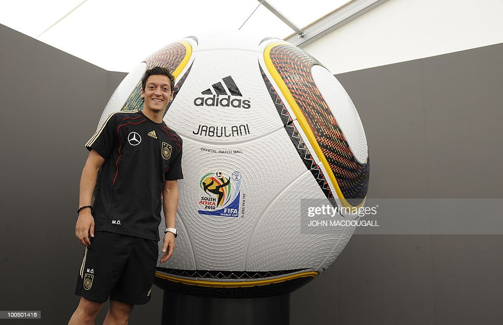 Germany's midfielder Mesut Oezil poses is front of a giant football during a press conference in Appiano, near the north Italian city of Bolzano May 25, 2010. The German football team is currently taking part in a 12-day training camp in Appiano to prepare for the upcoming FIFA Football World Cup in South Africa.