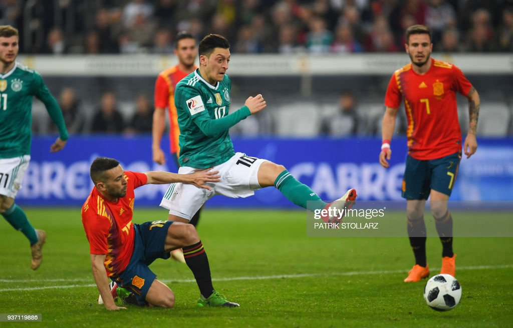Germany's midfielder Mesut Ozil (C) and Spain's defender Jordi Alba (L) vie for the ball during the international friendly football match of Germany vs Spain in Duesseldorf, western Germany, on March 23, 2018, in preparation of the 2018 Fifa World Cup. / AFP PHOTO / Patrik STOLLARZ