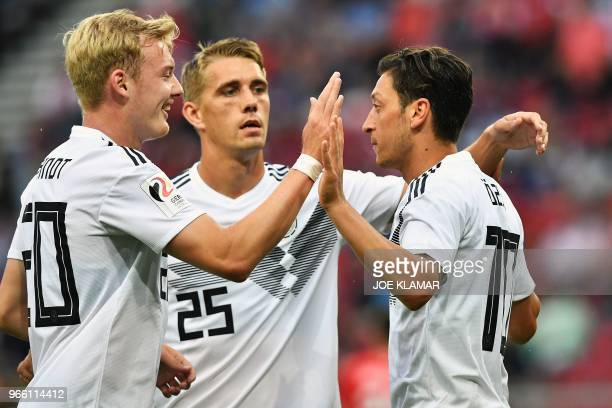 Germany's midfielder Mesut Ozil celebrates scoring the opening goal with Germany's midfielder Julian Brandt and Germany's forward Nils Petersen...