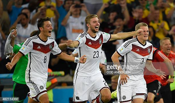 Germany's midfielder Mesut Ozil Germany's midfielder Christoph Kramer and Germany's defender Matthias Ginter celebrate after winning the 2014 FIFA...