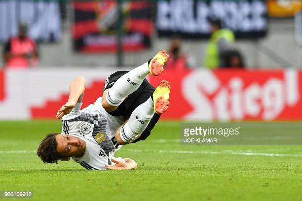 Germany's midfielder Mesut Ozil takes a tumble during the international friendly footbal match Austria v Germany in Klagenfurt Austria on June 2 2018