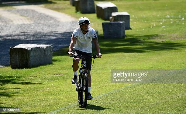 Germany's midfielder Mezut Ozil rides a bicycle as he arrives to take part in a training session as part of the team's preparation for the upcoming...
