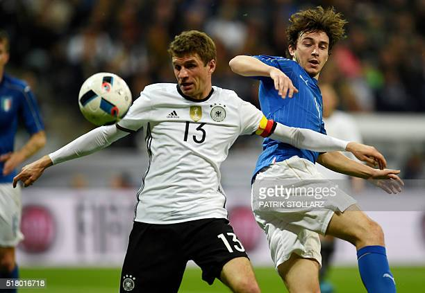 Germany's midfielder Thomas Mueller and Italy´s Matteo Darmian vie for the ball during the friendly football match Germany vs Italy in Munich...