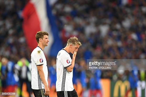 Germany's midfielder Thomas Mueller and midfielder Bastian Schweinsteiger leave the pitch after loosing 20 to France in the Euro 2016 semifinal...