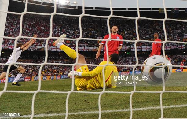 Germany's midfielder Thomas Mueller scores the third goal past England's goalkeeper David James during the 2010 World Cup round of 16 match Germany...
