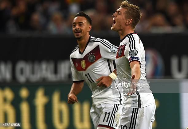 Germany's midfielder Toni Kroos and Germany´s midfielder Karim Bellarabi celebrate during the UEFA Euro 2016 Group D qualifying football match...