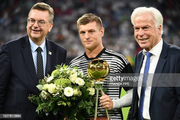 "Germany's midfielder Toni Kroos holds his ""Best player of the Year in Germany"" award next to President of the German Football Association Reinhard..."