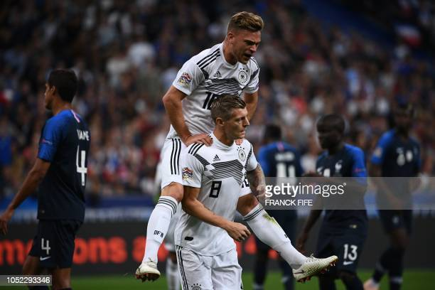 Germany's midfielder Toni Kroos is congratulated by Germany's midfielder Joshua Kimmich after scoring the opener on a penalty kick during the UEFA...
