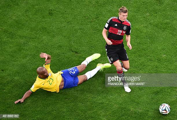 Germany's midfielder Toni Kroos jumps a tackle by Brazil's defender Maicon during the semifinal football match between Brazil and Germany at The...