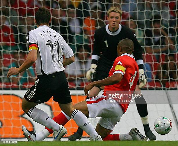 Germany's Miroslav Klose puts the ball past Wales Danny Gabbidon and Wales Goalkeeper Wayne Henessey to score the first goal of the match during...