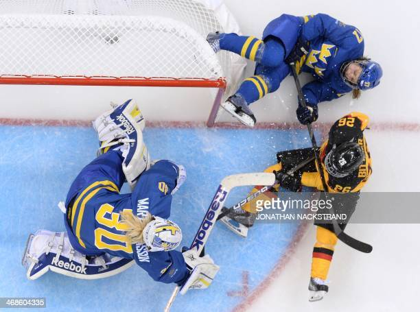 Germany's Monika Bittner tries to score against Sweden's goalkeeper Kim Martin Hasson and Sweden's Linnea Backman during the Women's Ice Hockey Group...