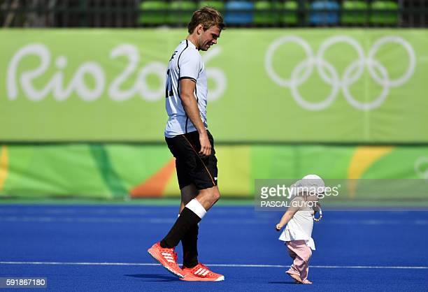 Germany's Moritz Furste walks on the pitch with his child after winning the men's Bronze medal field hockey Netherlands vs Germany match of the Rio...