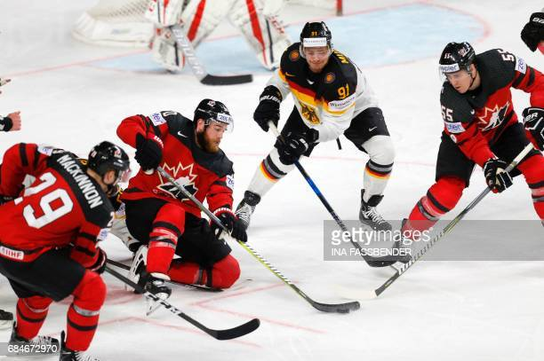 Germany's Moritz Mueller vies with Canada's Nate MacKinnon Ryan O'Reilly and Mark Scheifele during the IIHF Men's World Championship Ice Hockey...