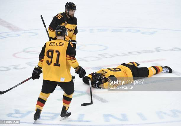 TOPSHOT Germany's Moritz Muller and Canada's Maxim Noreau check on teammate David Wolf as he lies on the ice after being hit in the men's semifinal...
