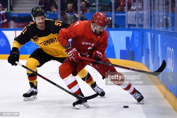 TOPSHOT Germany's Moritz Muller and Russia's Ivan Telegin fight for the puck in the men's gold medal ice hockey match between the Olympic Athletes...