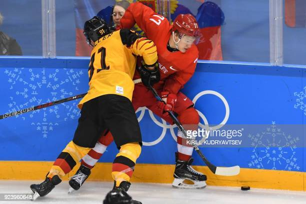 Germany's Moritz Muller and Russia's Kirill Kaprizov fight for the puck in the men's gold medal ice hockey match between the Olympic Athletes from...