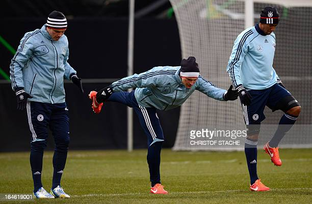Germany's national football players defender Heiko Westermann striker Mario Gomez and defender Jerome Boateng stretchs during the final trainings...