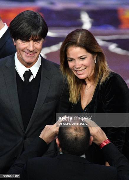 Germany's national football team coach Joachim Loew poses with Russian sports journalist and draw conductor Maria Komandnaya during the Final Draw...